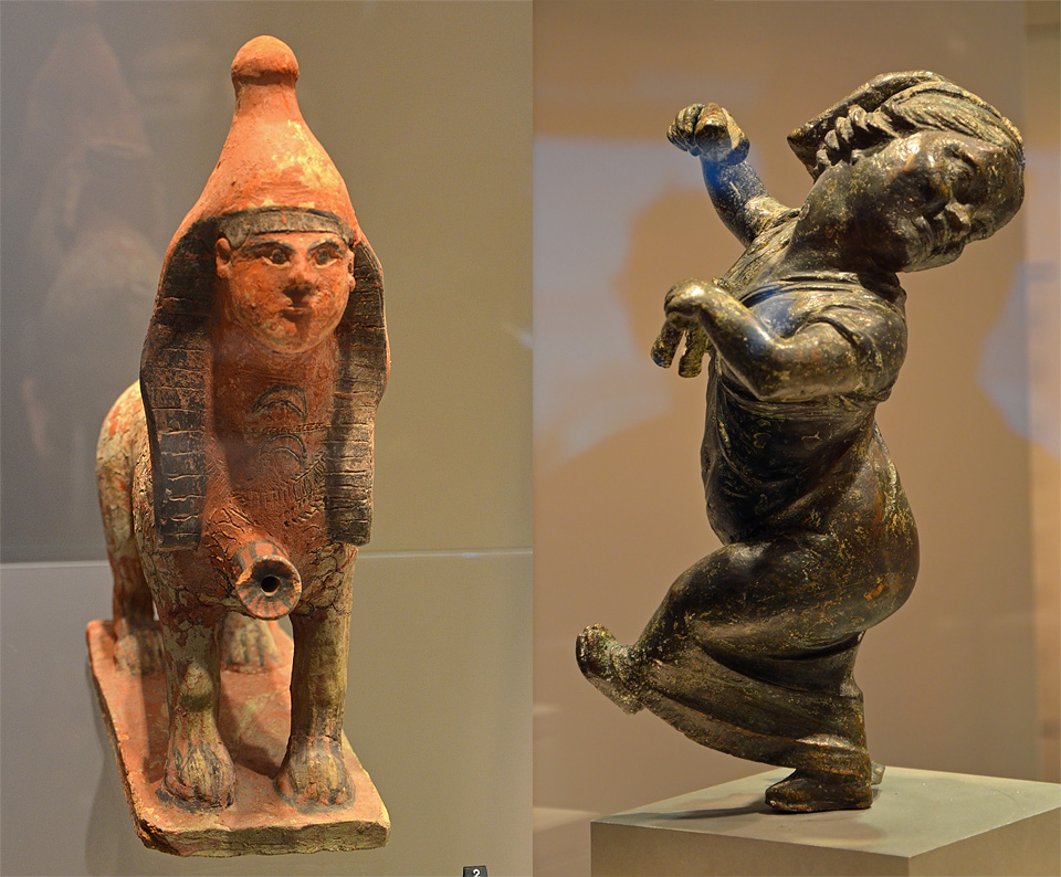 Links: vaas in de vorm van een sfinx (7e eeuw v.C.), rechts: dansende dwerg uit scheepswrak van Mahdia (150-100 v.C.) Deze vaas heeft de vorm van een sfinx met een Egyptisch kapsel